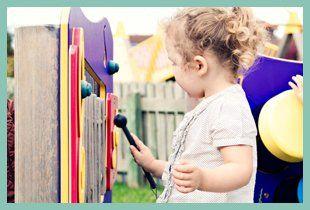 Girl playing a glockenspiel outside
