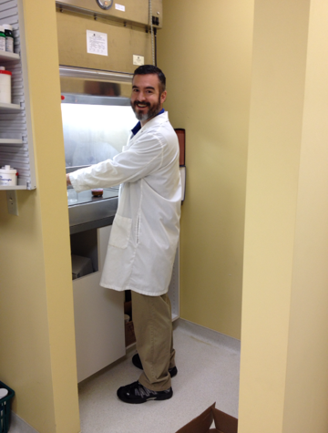 Happy pharmacist at work in pharmaceutical lab