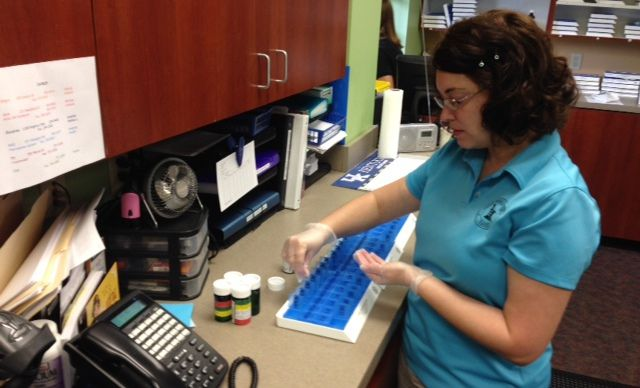 Sarah Volz, Medi-Planner for Jeff's Prescription Shop, measuring out medications