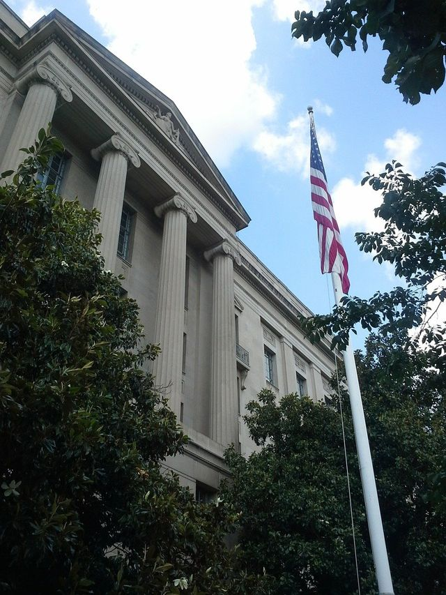 US Flag standing tall outside of a courthouse
