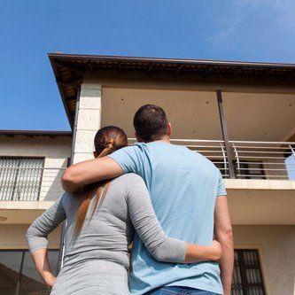 una coppia abbracciata mentre osserva una casa