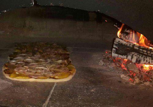 Vista interna del forno a legna acceso con un trancio di pizza farcita