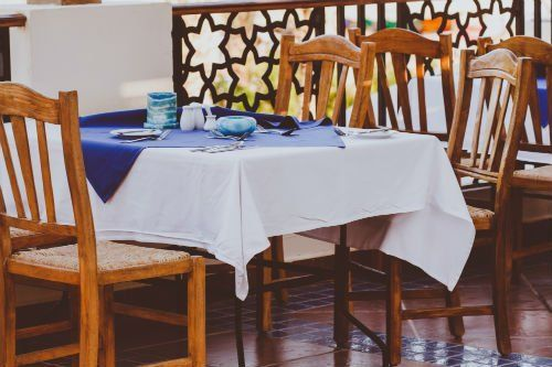 un tavolo con una tovaglia bianca e blu e delle sedie