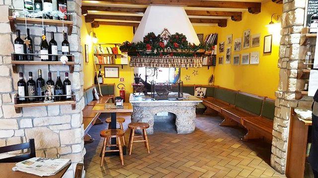 interno del ristorante con sulla sinistra dei vini esposti su delle mensole e al centro una struttura in marmo con in alto una cappa e dei fiori bianchi e rossi, delle panche di legno e dei tavoli con delle sedie