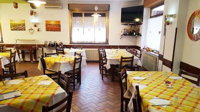 sala da pranzo del ristorante con tavoli apparecchiati con tovaglie gialle a quadretti arancioni