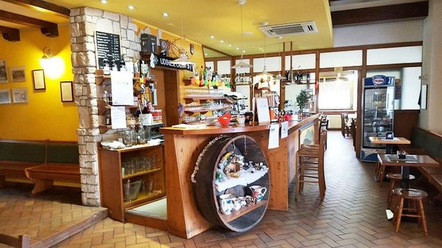 interno del ristorante con sulla sinistra un bancone in legno con dietro la zona bar, di fronte delle sedie e dei tavoli in legno e il frigorifero con dentro le bibite