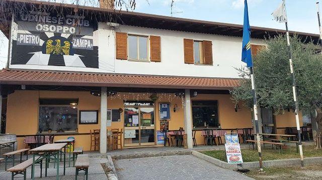 il ristorante visto da fuori con un giardino con dei tavoli e sull'edificio uno striscione con scritto Udinese Club