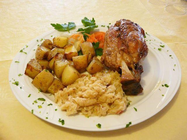 un piatto di arrosto con patate, foglie di prezzemolo,carote e dell'altra verdura