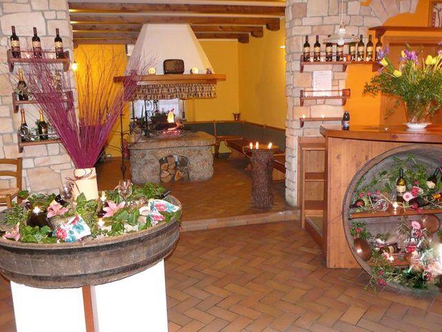 una struttura di marmo con sopra dei fiori e un vaso con dentro dei rami artificiali bordeaux, sulla destra un insenatura rotonda in un mobile con dentro dei fiori e davanti,in fondo un forno a legna con una cappa bianca sul soffitto