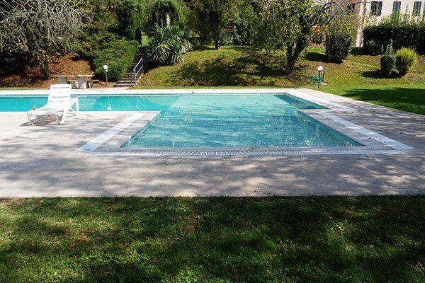 una piscina in un giardino e una sdraio di plastica di color bianco