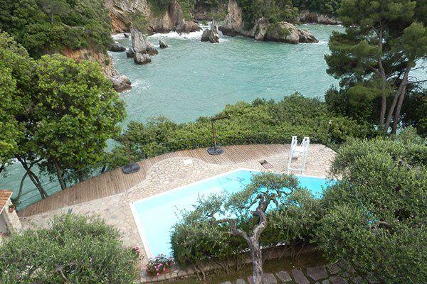 visuale aerea di una piscina in un giardino con degli alberi e più avanti un fiume e delle rocce