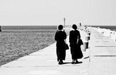 Due donne in lutto camminano sopra una banchina