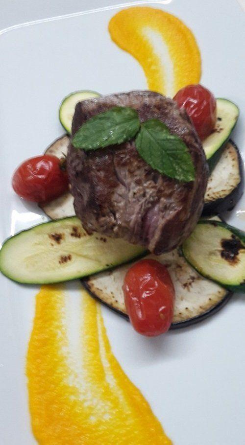 un piatto a base di carne, zucchine e pomodorini