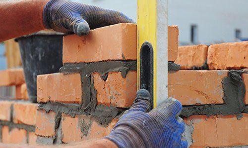 un muratore sta misurando dei mattoni appena posizionati con la livella