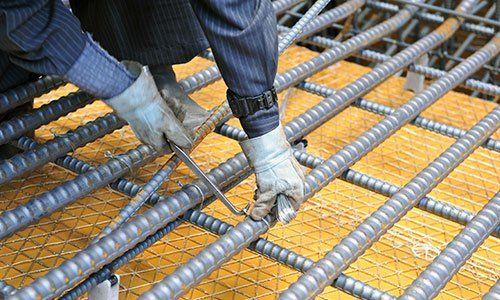 due mani con dei guanti da lavoro che stanno stringendo un telaio in ferro