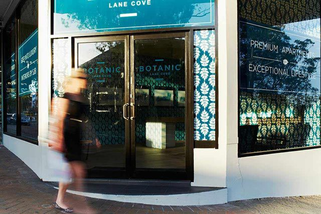 blurred women walking in front of blue lane cove sign