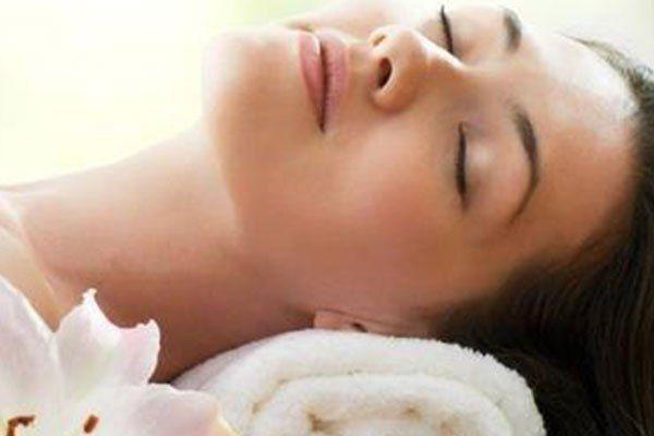Una donna sdraiata mentre appoggia il collo su un asciugamano di color bianco