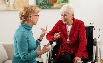 A lady talking to an older lady in a wheelchair
