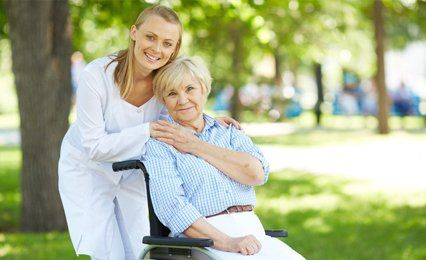 A young lady with her arms round her Mum who is in a wheelchair