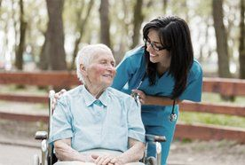 A young lady smiling at an older lady in a wheelchair