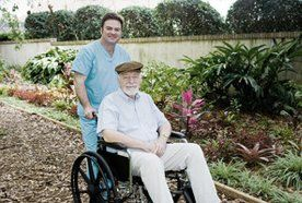 A carer pushing a man in a wheelchair around the garden
