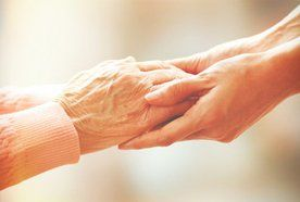 Elderly hands clasped in younger ones