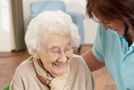 An elderly lady laughing with a carer
