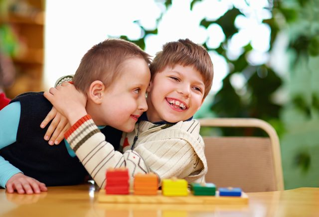 A little boy with his arms around another child, sitting at a table in front of a coloured shape-sorter