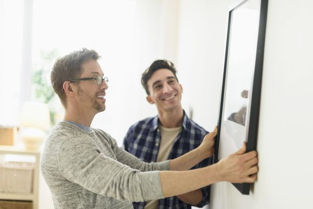 Two men hanging a picture on a wall