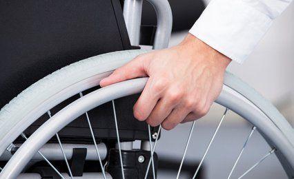 A hand on a wheelchair wheel