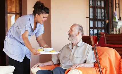 A carer serving breakfast on a tray to a man sitting in an armchair