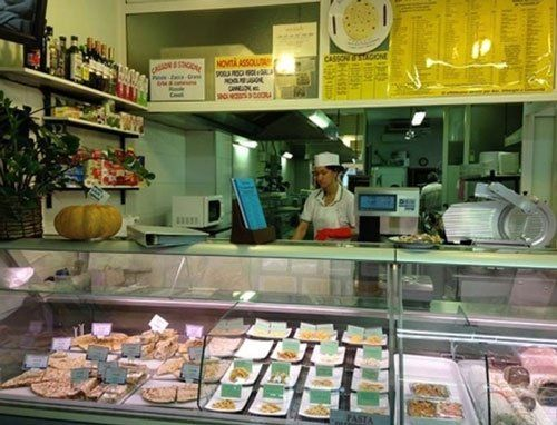 una vetrina con piatti pronti e una donna dietro il banco
