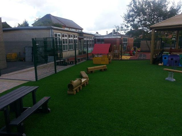 Play area constructed from safety grass matting