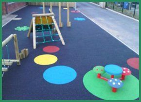 Colourful play area for little children, with climbing frame and table and chairs in the shape of mushrooms