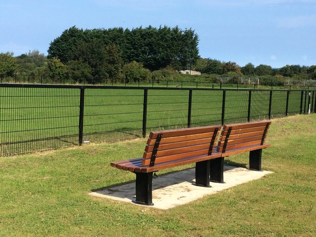 A wooden bench overlooking a sports pitch