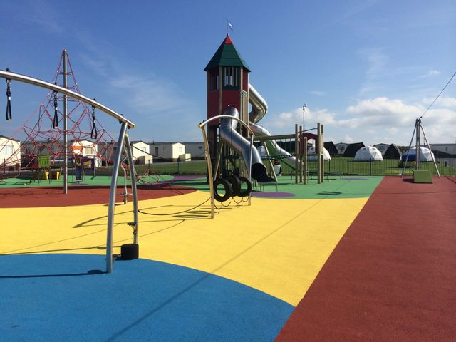 A play area with surfaces painted teal, yellow, green and terracotta