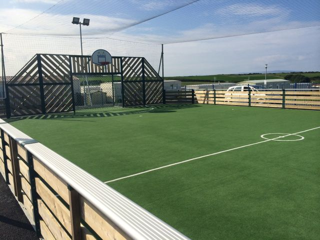 A timber fence around a green sports pitch