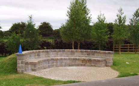 A curved stone wall on a circular paved area