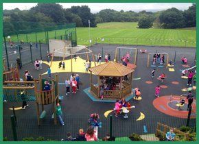 Children having fun in a tarmac outdoor play area with swings, slides and climbing frames