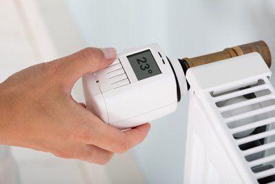 primo piano di un termostato radiatore con mano della donna