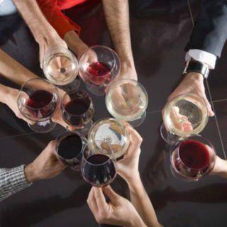 delle mani con dei bicchieri di vino