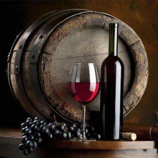 un bicchiere di vino rosso, una bottiglia e un barile