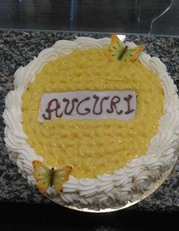 una torta con panna e crema pasticcera con scritto Auguri