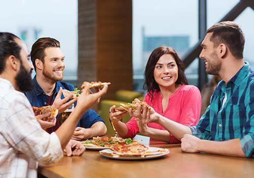 quattro amici che mangiano pizza al ristorante