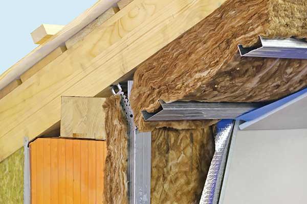 un modellino in legno di un tetto sorretto da delle travi in ferro, con materiale per isolamento insufflato