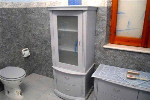 Dei mobili di color grigio in un bagno