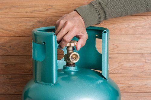 persona accende una bombola a gas
