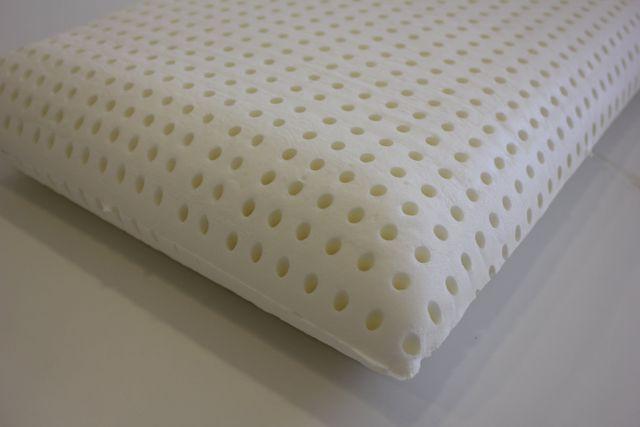 Un letto di color grigio con copriletto e cuscini di color crema, una lampada da terra di color bianco e un vaso nero