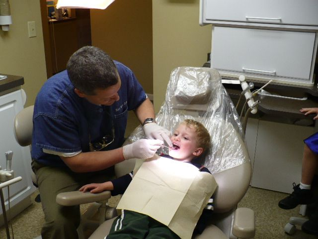 dentist speaking with child patient and mother