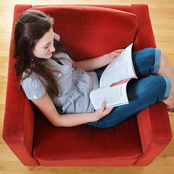 Young woman sitting in a red love seat, reading her Vancouver travel guide